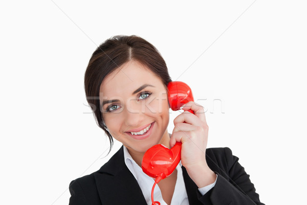 Smiling woman in suit using a red dial telephone against white background Stock photo © wavebreak_media