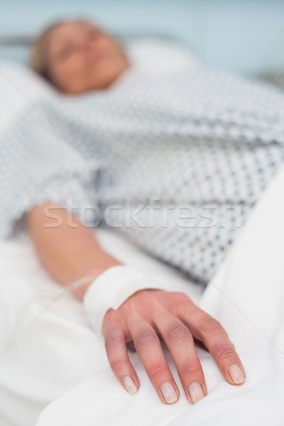 Focus on the hand of a patient lied on a bed in hospital ward Stock photo © wavebreak_media