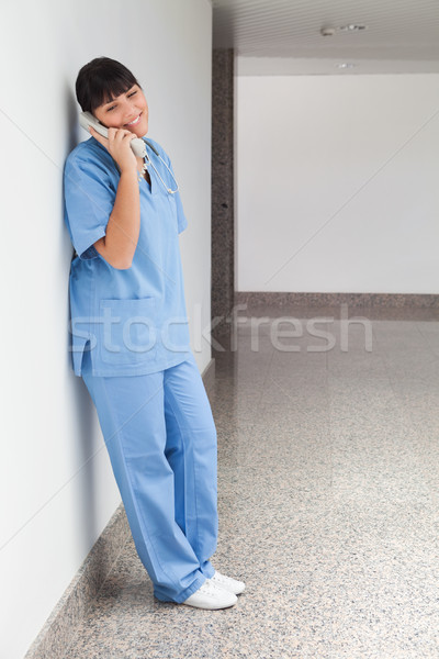 Stock photo: Smiling nurse on telephone in hospital corridor