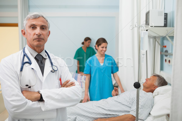 Doctor with folded arms in hospital room with two nurses and a patient in the background Stock photo © wavebreak_media