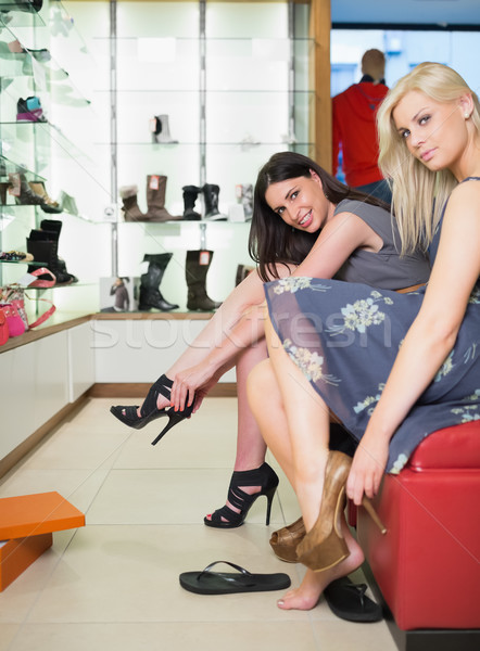 Women smiling and trying on shoes in shoe store Stock photo © wavebreak_media