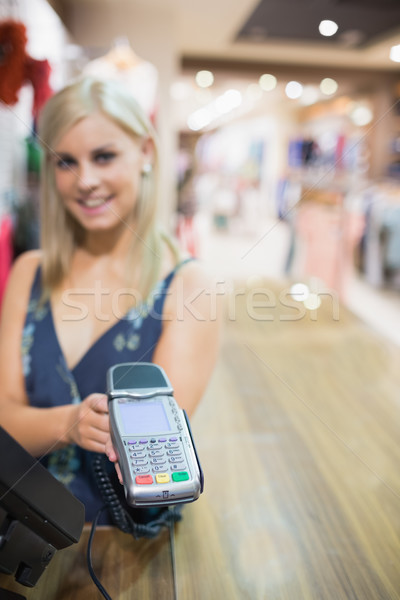 Smiling woman holding credit card machine in clothes store Stock photo © wavebreak_media