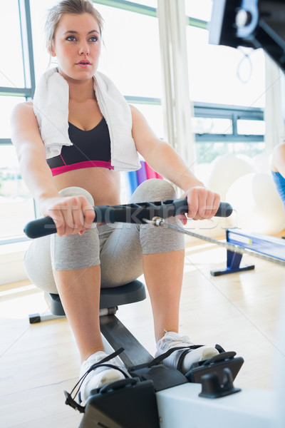 Young woman on the row machine in fitness studio Stock photo © wavebreak_media