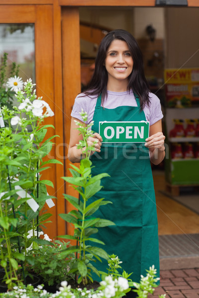 Garden center worker holding open sign at entrance to garden center Stock photo © wavebreak_media