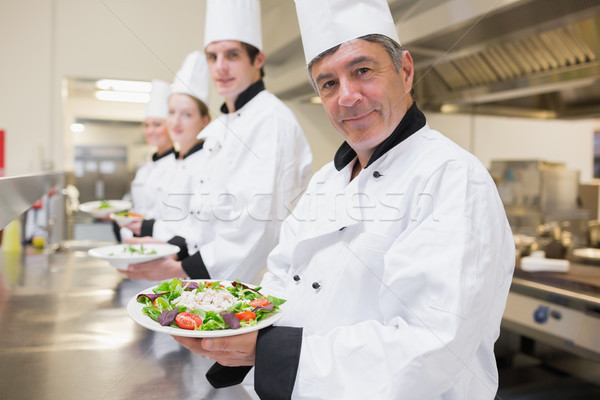 Cheerful Chef's showing their salads in the kitchen  Stock photo © wavebreak_media