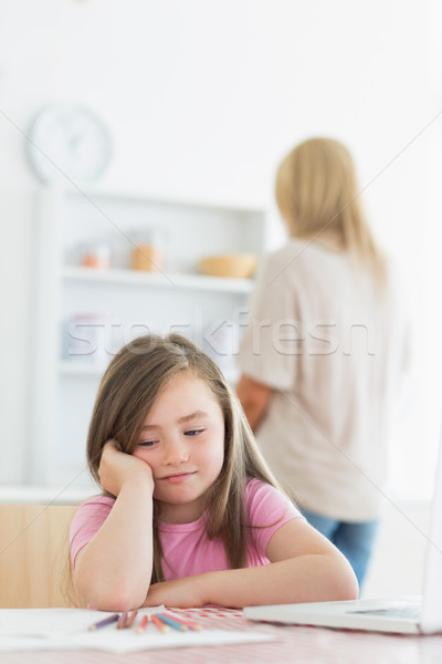 Stock photo: Little girl bored with drawing with mother in background