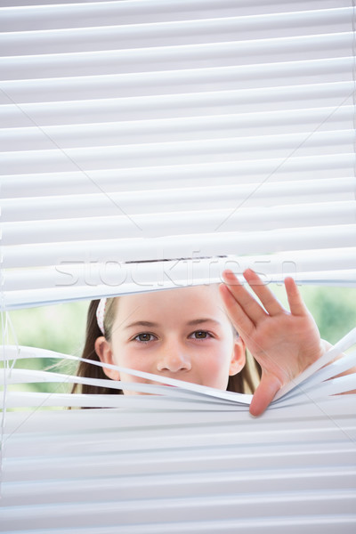 Little girl peeking through blinds Stock photo © wavebreak_media