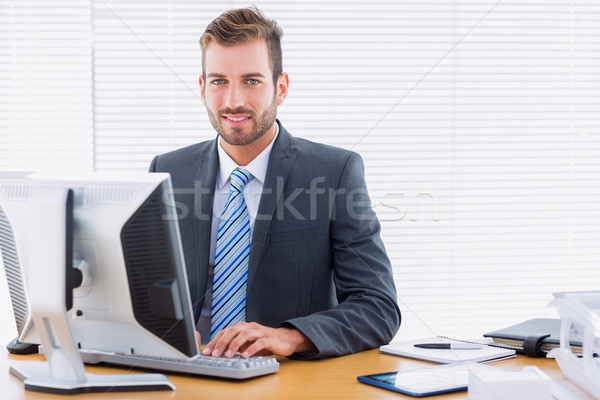 Young businessman using computer at office desk Stock photo © wavebreak_media
