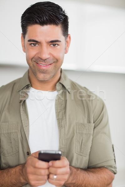 Smiling man text messaging Stock photo © wavebreak_media