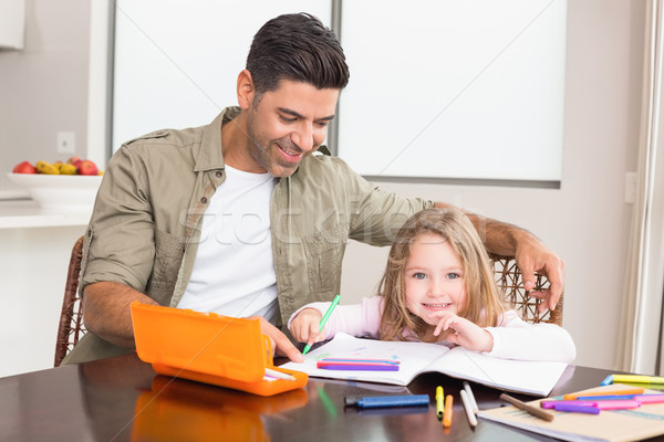 Cheerful little girl colouring at the table with her father Stock photo © wavebreak_media