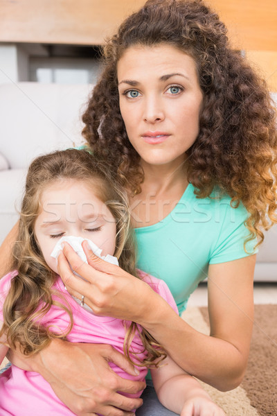 Worried mother helping her little daughter blow her nose Stock photo © wavebreak_media