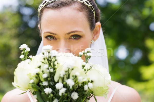 Bride peeking over bouquet in garden Stock photo © wavebreak_media