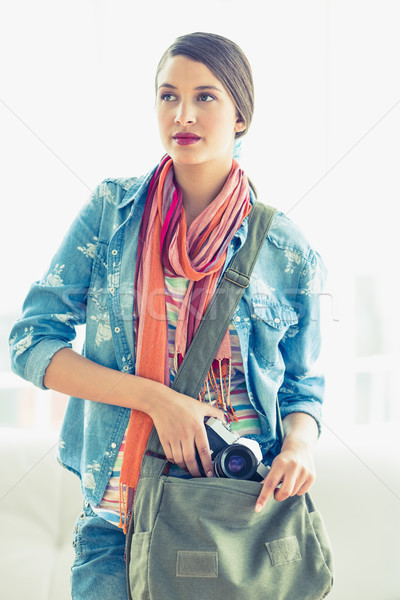 Young thinking woman taking camera from her bag Stock photo © wavebreak_media