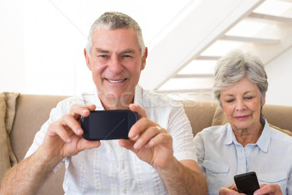 Senior couple sitting on couch using their smartphones Stock photo © wavebreak_media
