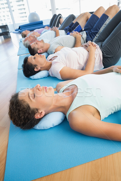 Class resting on mats in row at yoga class Stock photo © wavebreak_media