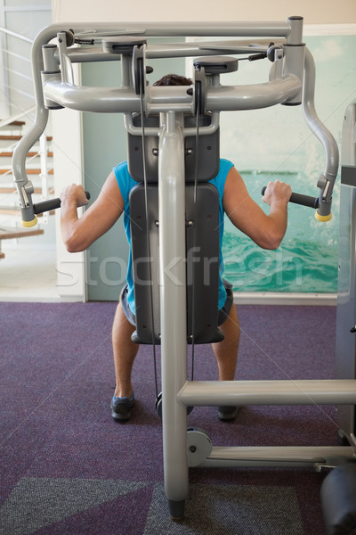 Focused man using weights machine for arms Stock photo © wavebreak_media