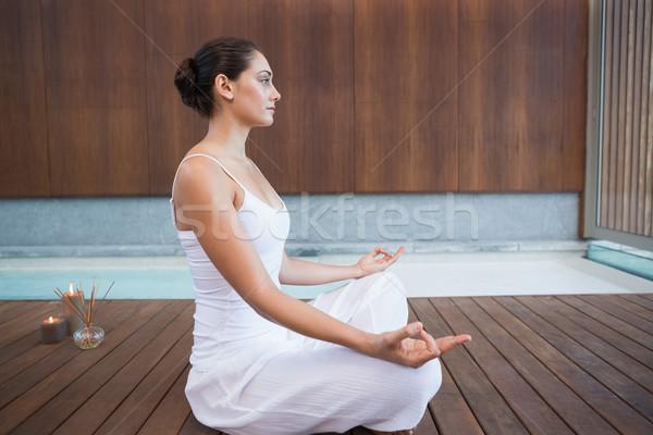 Peaceful brunette in white sitting in lotus pose  Stock photo © wavebreak_media