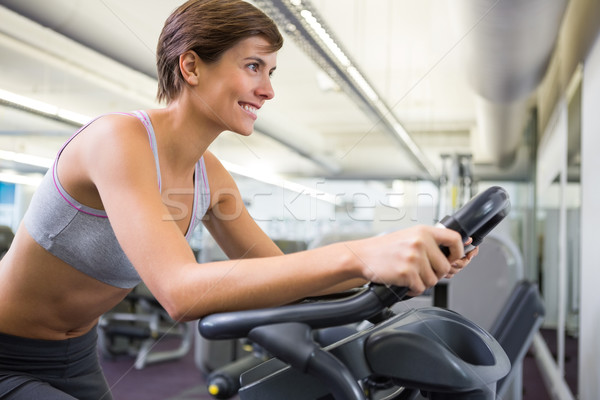 Stock photo: Fit woman working out on the exercise bike