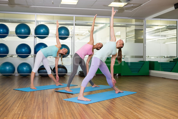Yoga class in extended traingle position in fitness studio Stock photo © wavebreak_media