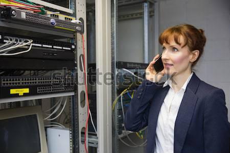 Pretty computer technician smiling at camera beside server Stock photo © wavebreak_media