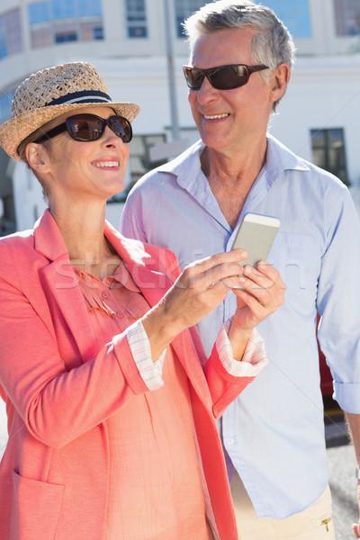 Happy senior couple looking at smartphone holding shopping bags Stock photo © wavebreak_media