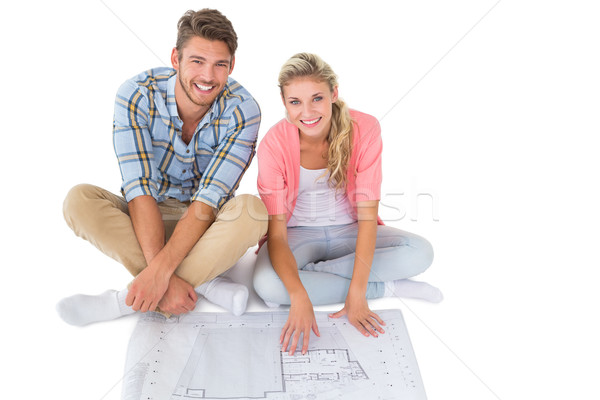 Attractive young couple sitting looking at blueprint Stock photo © wavebreak_media