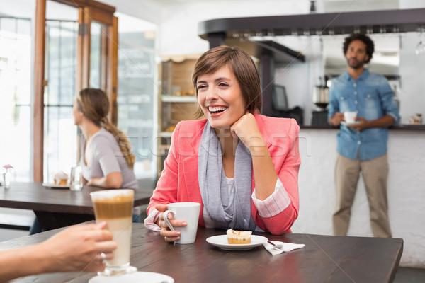 Pretty brunette enjoying her latte with a friend Stock photo © wavebreak_media