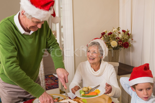 Grandfather in santa hat serving roast turkey at christmas Stock photo © wavebreak_media