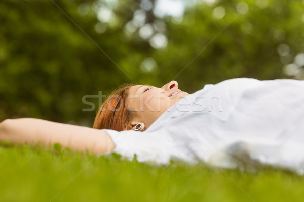 Pretty redhead smiling and lying Stock photo © wavebreak_media