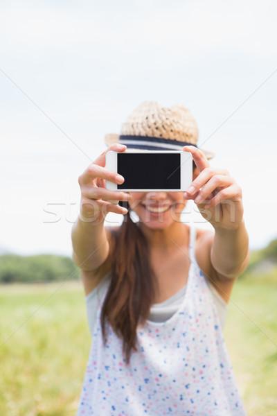 Pretty brunette taking a selfie in park Stock photo © wavebreak_media