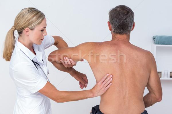 Doctor examining her patient arm Stock photo © wavebreak_media