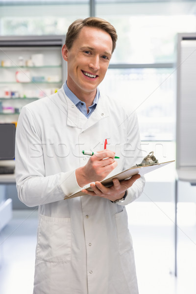 Handsome pharmacist writing on clipboard Stock photo © wavebreak_media