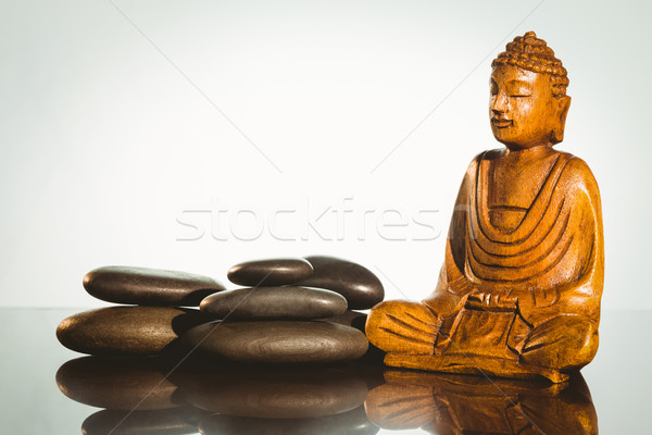 Wooden buddha statue with balancing pebbles Stock photo © wavebreak_media