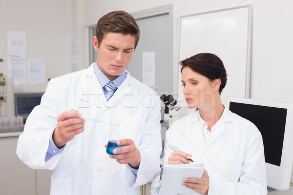 Científicos examinar azul fluido laboratorio mujer Foto stock © wavebreak_media