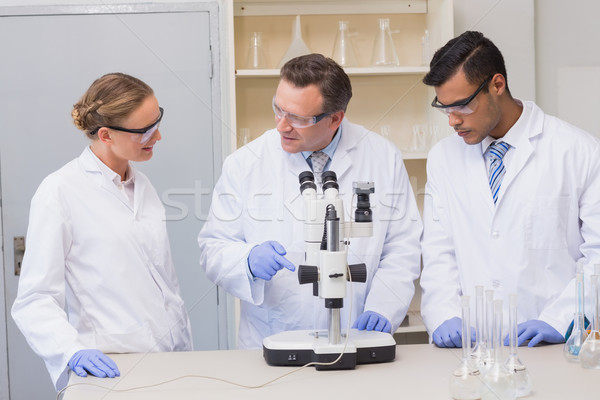 Concentrated scientists working together with microscope Stock photo © wavebreak_media