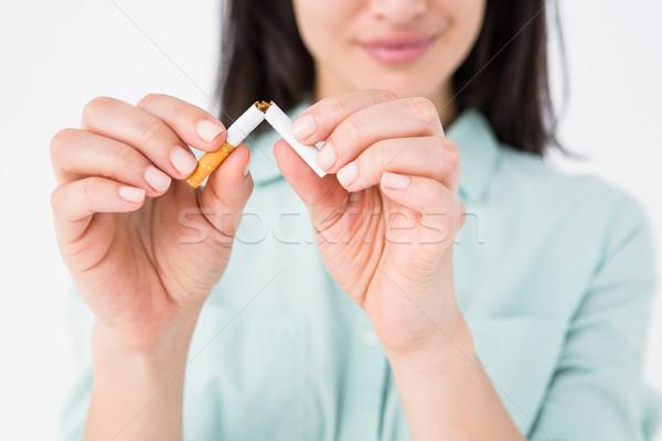 Smiling woman snapping cigarette in half Stock photo © wavebreak_media