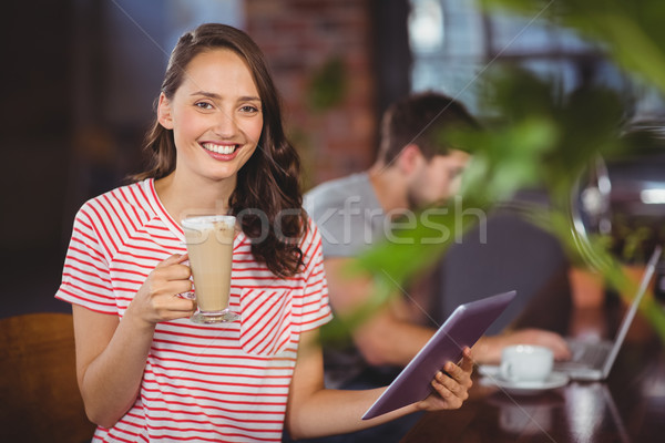 Smiling young woman enjoying latte and using tablet computer Stock photo © wavebreak_media