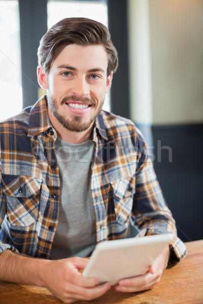 Handsome young man holding tablet pc Stock photo © wavebreak_media