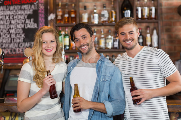 Felice amici posa birra bottiglie pub Foto d'archivio © wavebreak_media