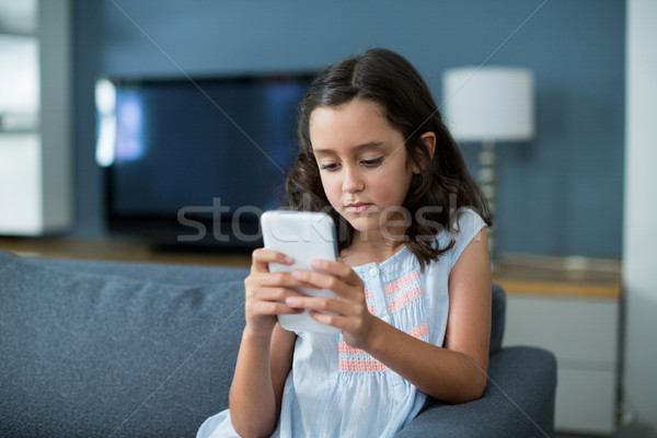 Unhappy girl sitting on sofa and using mobile phone in living room Stock photo © wavebreak_media