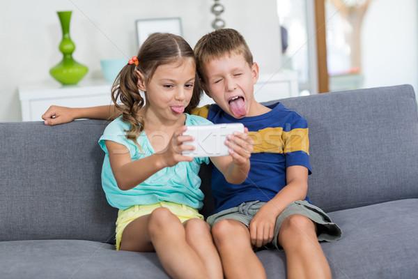 Testvérek elvesz mobiltelefon nappali otthon boldog Stock fotó © wavebreak_media