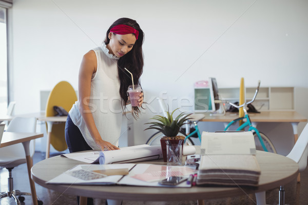 Businesswoman holding drink while working at office desk Stock photo © wavebreak_media