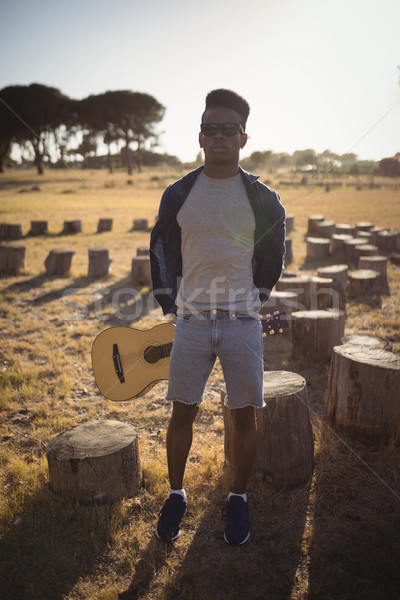 Stock photo: Full length of man holding guitar while standing at forest