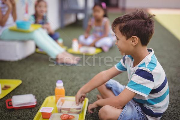 Heureux écolier repas école fille herbe Photo stock © wavebreak_media