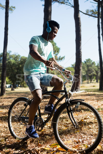 Man with headphones riding bicycle in the park Stock photo © wavebreak_media