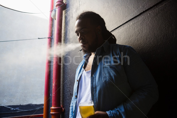 Man having beer while smoking Stock photo © wavebreak_media
