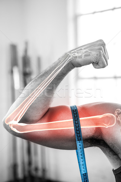 Highlighted arm of man measuring biceps with measuring tape Stock photo © wavebreak_media