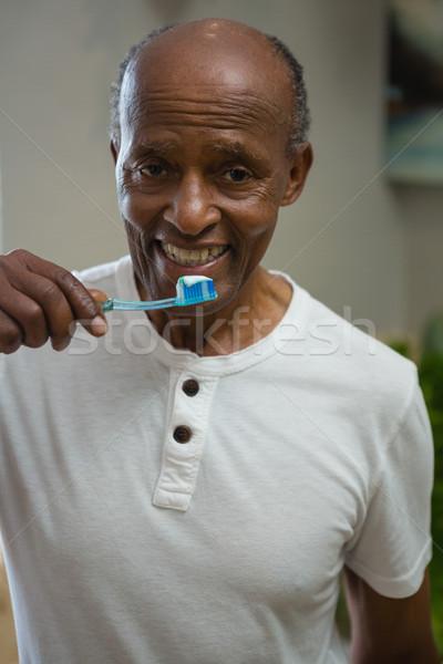 Portrait of smiling senior man brushing teeth in bathroom at home Stock photo © wavebreak_media