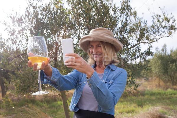 Woman taking a photo of wine glass in olives farm Stock photo © wavebreak_media