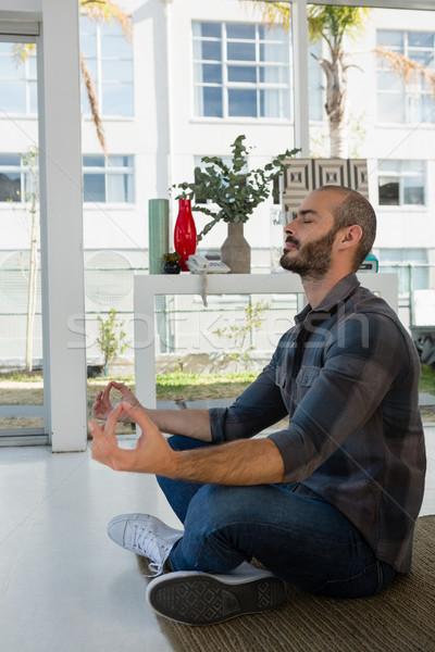 Businessman meditating while sitting on floor Stock photo © wavebreak_media